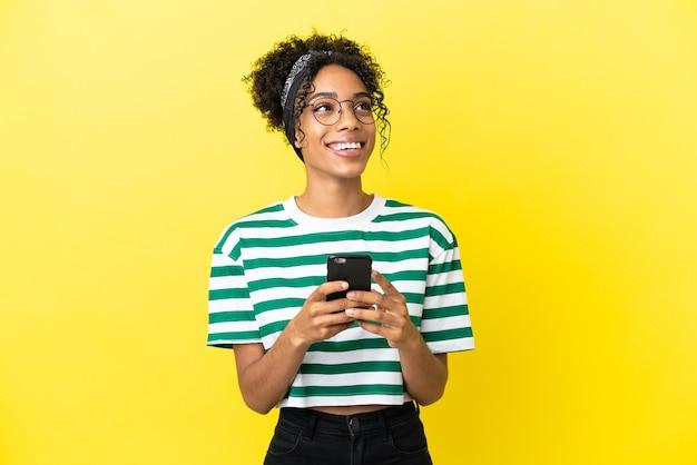 Молодая афро-американская женщина изолирована на желтом фоне с помощью мобильного телефона и смотрит вверх