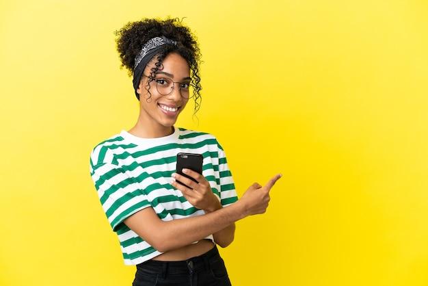 Молодая афро-американская женщина изолирована на желтом фоне, используя мобильный телефон и указывая назад