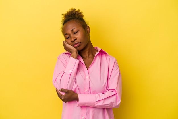退屈、疲れ、リラックスした日を必要とする黄色の背景に孤立した若いアフリカ系アメリカ人女性。
