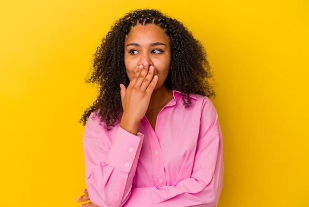 黄色い背景にあくびをした若いアフリカ系アメリカ人女性は、手で口を覆っている疲れたジェスチャーを示しています。