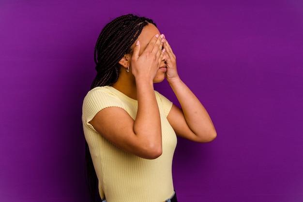 黄色の背景に分離された若いアフリカ系アメリカ人女性黄色の背景に分離された若いアフリカ系アメリカ人女性は手で目を覆うことを恐れています。