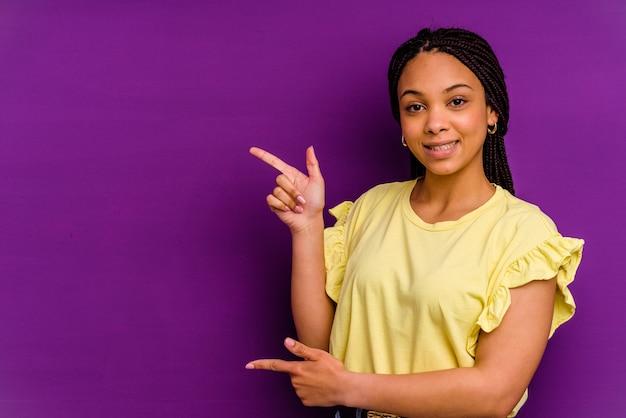 黄色の背景に分離された若いアフリカ系アメリカ人女性黄色の背景に分離された若いアフリカ系アメリカ人女性は、離れて人差し指を指して興奮しました。