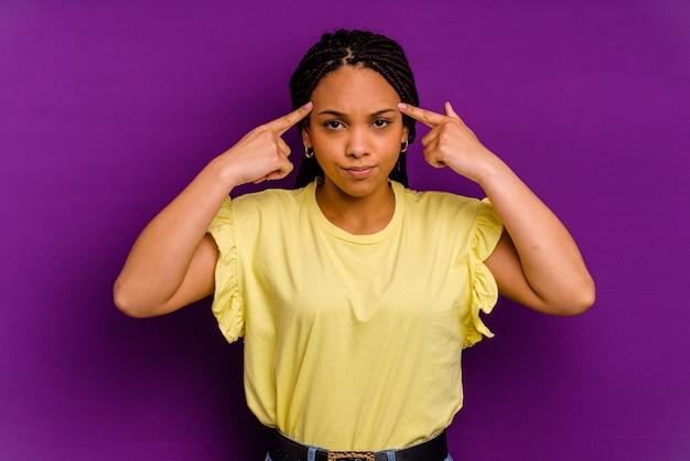 Молодая афро-американская женщина, изолированных на желтом фоне молодая афро-американская женщина, изолированных на желтом фоне сосредоточилась на задаче, держа указательные пальцы, указывая головой.