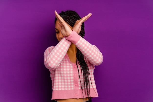 黄色の背景に分離された若いアフリカ系アメリカ人女性黄色の背景に分離された若いアフリカ系アメリカ人女性は、2つの腕を交差させたまま、概念を否定します。