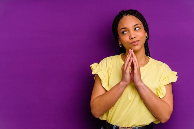 黄色の背景に分離された若いアフリカ系アメリカ人女性黄色の背景に分離された若いアフリカ系アメリカ人女性は、計画を立てて、アイデアを設定します。