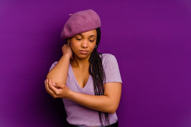 黄色の背景で隔離の若いアフリカ系アメリカ人女性肘をマッサージし、悪い動きの後に苦しんでいる黄色の背景で隔離の若いアフリカ系アメリカ人女性。