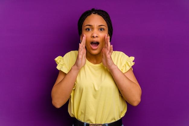 黄色の背景に分離された若いアフリカ系アメリカ人女性黄色の背景に分離された若いアフリカ系アメリカ人女性が正面に興奮して叫んでいます。