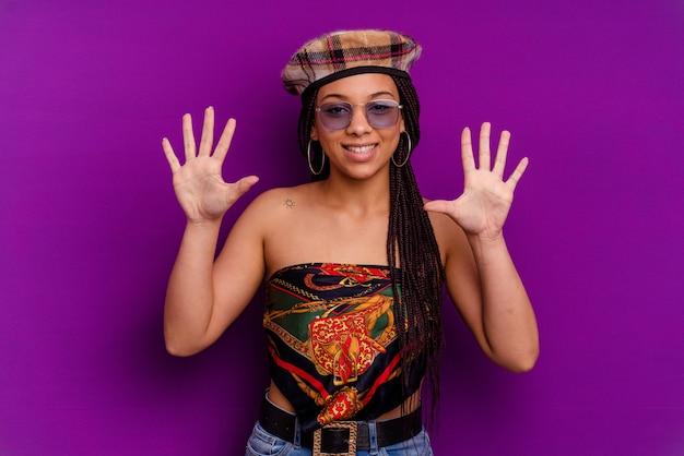 黄色の背景に分離された若いアフリカ系アメリカ人女性黄色の背景に分離された若いアフリカ系アメリカ人女性は、手で10番を示しています。