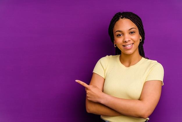 黄色の背景に分離された若いアフリカ系アメリカ人女性黄色の背景に分離された若いアフリカ系アメリカ人女性は人差し指を離れて元気に指して笑っています。