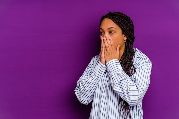黄色の背景に分離された若いアフリカ系アメリカ人女性黄色の背景に分離された若いアフリカ系アメリカ人女性は、手で口を覆うコピースペースを思慮深く探しています。