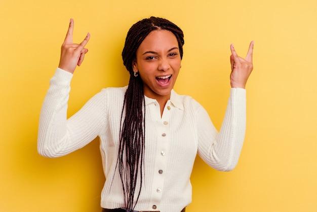 혁명 개념으로 뿔 제스처를 보여주는 노란색에 고립 된 젊은 아프리카 계 미국인 여자.