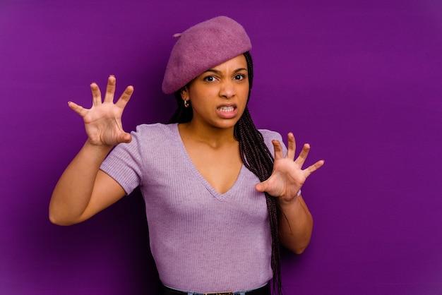 猫を模倣した爪、攻撃的なジェスチャーを示す黄色で隔離された若いアフリカ系アメリカ人の女性。