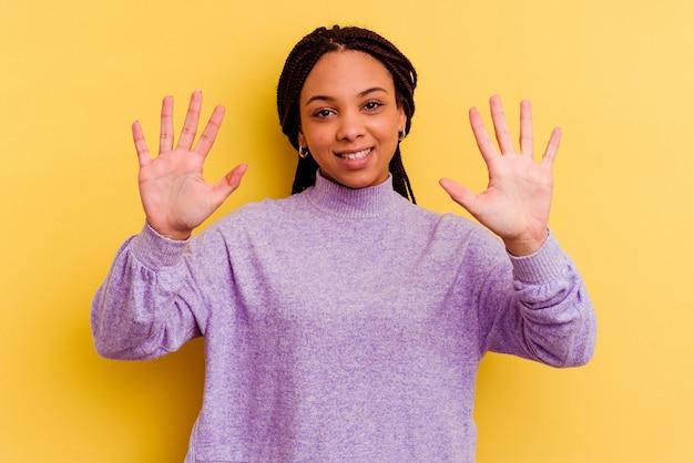 黄色で隔離された若いアフリカ系アメリカ人の女性は、手で10番を示しています。