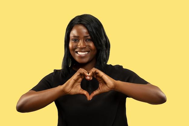 Молодая афро-американская женщина, изолированные на желтом пространстве, выражение лица. красивый женский поясной портрет.