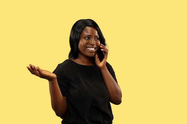 黄色の空間、表情で孤立した若いアフリカ系アメリカ人女性。美しい女性の半身像。