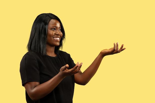 黄色のスタジオの背景、顔の表情に分離された若いアフリカ系アメリカ人の女性。美しい女性の半身像。人間の感情、顔の表情の概念。選択して招待します。