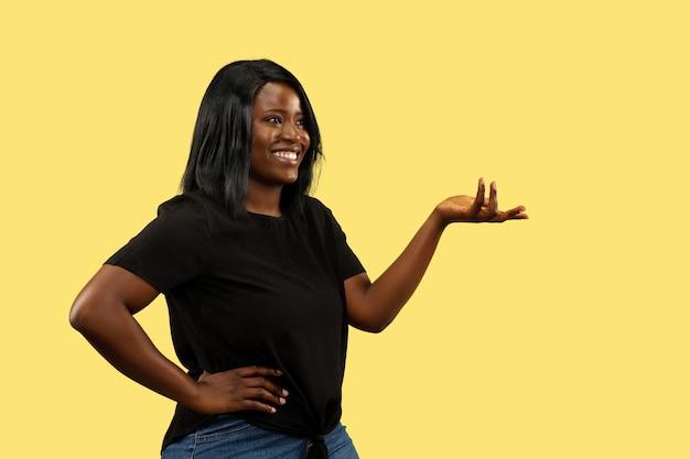 黄色のスタジオの背景、顔の表情に分離された若いアフリカ系アメリカ人女性。美しい女性のハーフレングスの肖像画。人間の感情、顔の表情の概念。選択して招待します。