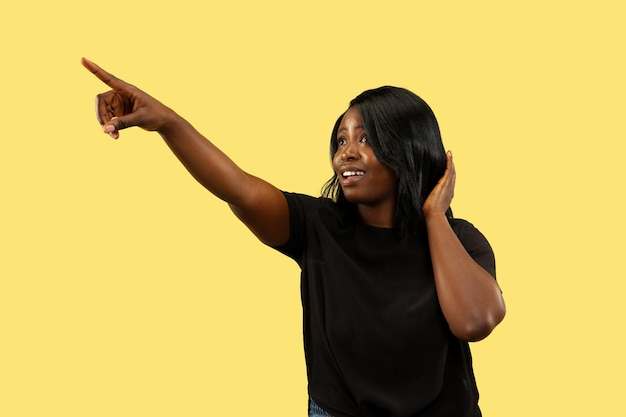 黄色のスタジオの背景、顔の表情に分離された若いアフリカ系アメリカ人女性。美しい女性のハーフレングスの肖像画。人間の感情、顔の表情の概念。選択して上向きにします。