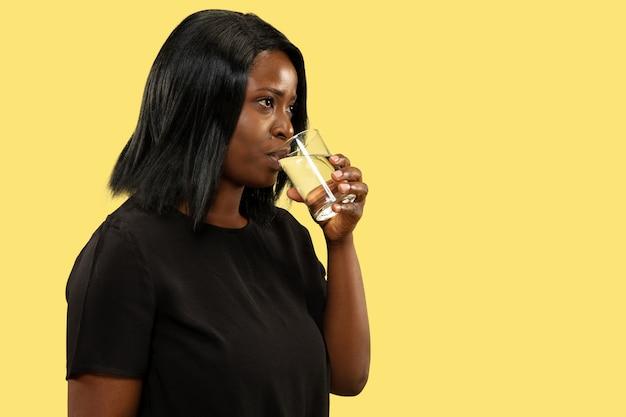 노란색 스튜디오 배경, 표정에 고립 된 젊은 아프리카 계 미국인 여자. 아름 다운 여성 절반 길이 초상화. 인간의 감정, 표정의 개념. 물을 마시고 웃고.