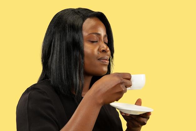 노란색 스튜디오 배경, 표정에 고립 된 젊은 아프리카 계 미국인 여자. 아름 다운 여성 절반 길이 초상화. 인간의 감정, 표정의 개념. 커피 마시기.