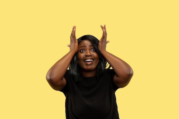 黄色のスタジオの背景、顔の表情に分離された若いアフリカ系アメリカ人女性。美しい女性のハーフレングスの肖像画。人間の感情、顔の表情の概念。エキサイティングで驚いた。