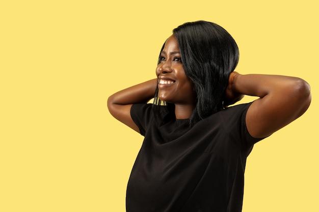 黄色のスタジオの背景、顔の表情に分離された若いアフリカ系アメリカ人の女性。美しい女性の半身像。人間の感情、顔の表情の概念。休憩と笑顔。