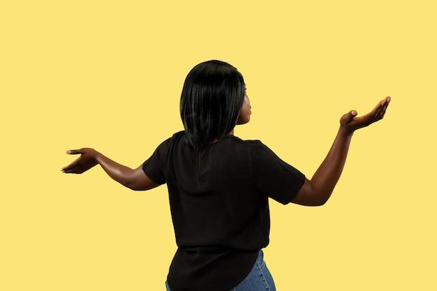 黄色のスタジオの背景、顔の表情に分離された若いアフリカ系アメリカ人女性。美しい女性のハーフレングスの肖像画。人間の感情、顔の表情の概念。空のバーを表示しています。
