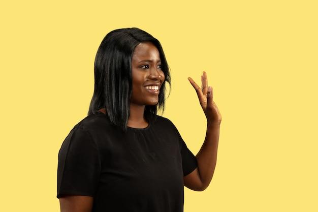 黄色のスタジオの背景、顔の表情に分離された若いアフリカ系アメリカ人女性。美しい女性のハーフレングスの肖像画。人間の感情、顔の表情の概念。さようならのサインを示しています。