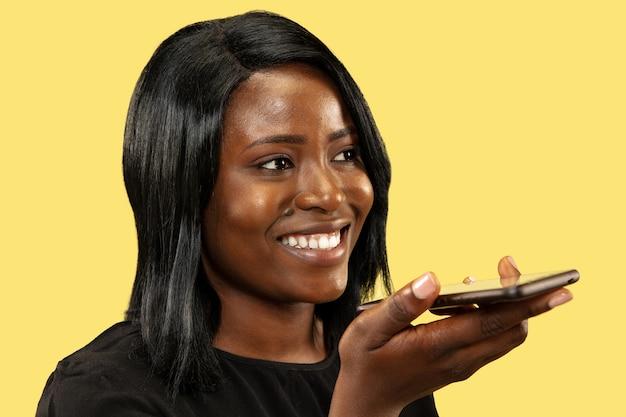 黄色のスタジオの背景、顔の表情に分離された若いアフリカ系アメリカ人の女性。女性の肖像画。人間の感情、顔の表情の概念。スマートフォンで話したり、音声メッセージを録音したりします。