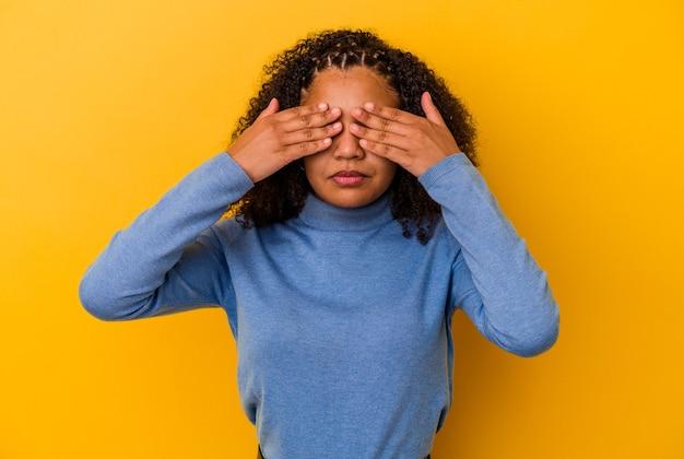 手で目を覆うことを恐れて黄色の壁に孤立した若いアフリカ系アメリカ人の女性。