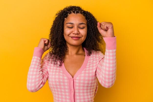 勝利、情熱と熱意、幸せな表現を祝う黄色の壁に孤立した若いアフリカ系アメリカ人の女性。