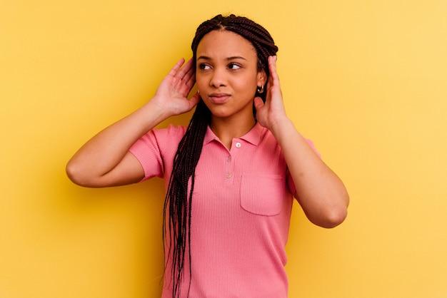 손가락으로 귀를 덮고 노란색 벽에 고립 된 젊은 아프리카 계 미국인 여자 스트레스와 큰 소리로 주변에 의해 필사적.