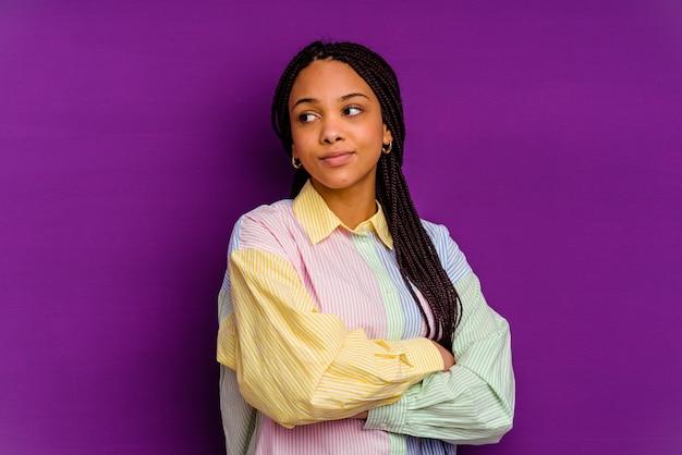 목표와 목적을 달성하는 꿈을 꾸고 노란색 벽에 고립 된 젊은 아프리카 계 미국인 여자