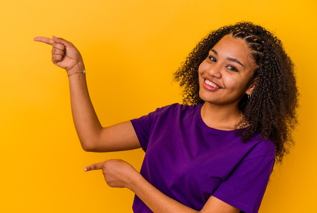 黄色の壁に孤立した若いアフリカ系アメリカ人の女性は、人差し指を離れて指差して興奮しました。
