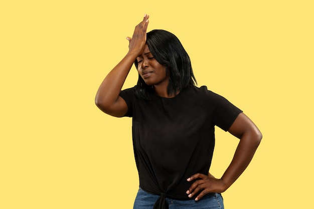 黄色の壁、顔の表情で隔離の若いアフリカ系アメリカ人の女性。美しい女性の半身像。人間の感情、顔の表情の概念。悲しみと痛み。