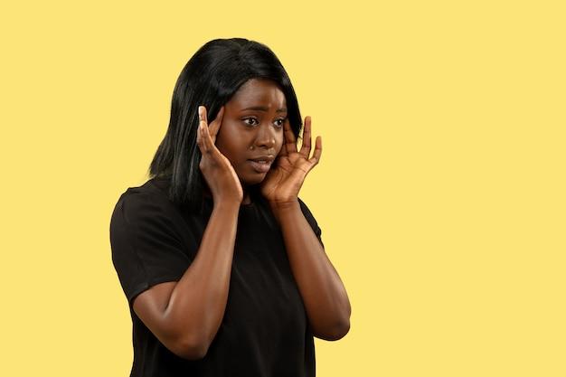 黄色の壁、顔の表情で隔離の若いアフリカ系アメリカ人の女性。美しい女性の半身像。人間の感情、顔の表情の概念。頭痛に苦しんでいます。