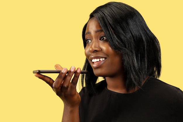黄色の壁、顔の表情で隔離の若いアフリカ系アメリカ人の女性。女性の肖像画。人間の感情、顔の表情の概念。スマートフォンで話したり、音声メッセージを録音したりします。