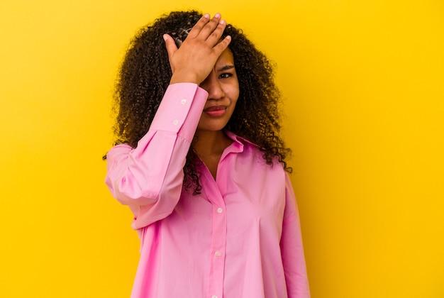 何かを忘れて、手のひらで額を叩き、目を閉じて、黄色の壁に孤立した若いアフリカ系アメリカ人の女性。