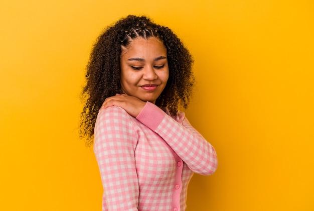肩の痛みを抱えている黄色の壁に孤立した若いアフリカ系アメリカ人女性。