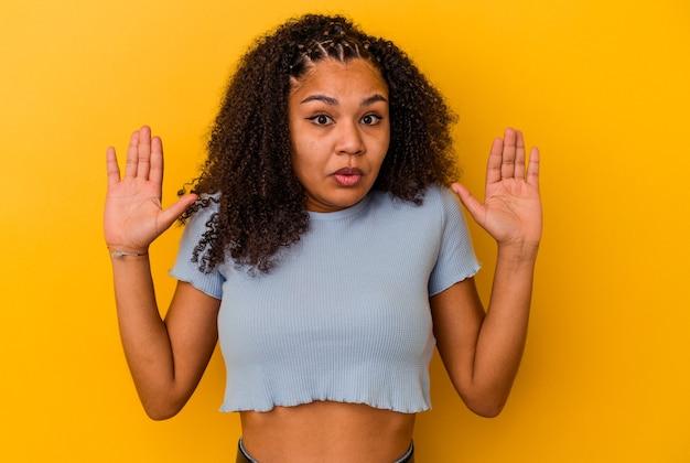 アイデア、インスピレーションの概念を持っている黄色の壁に分離された若いアフリカ系アメリカ人の女性。