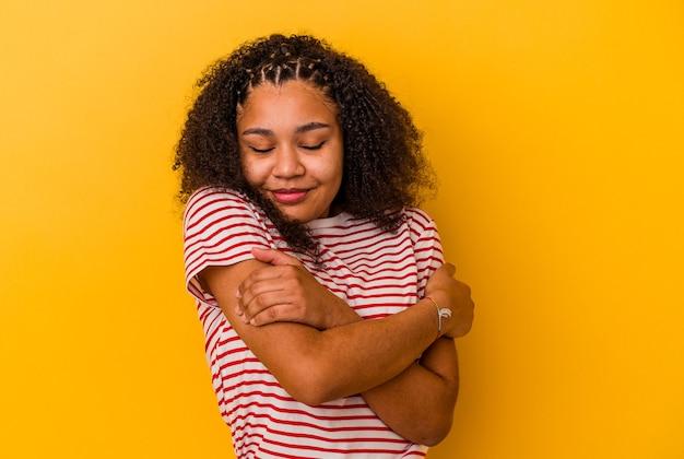 노란색 벽 포옹에 고립 된 젊은 아프리카 계 미국인 여자, 평온하고 행복 미소