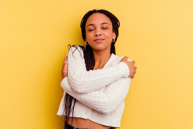 黄色の壁の抱擁に分離された若いアフリカ系アメリカ人の女性、のんびりと幸せな笑顔