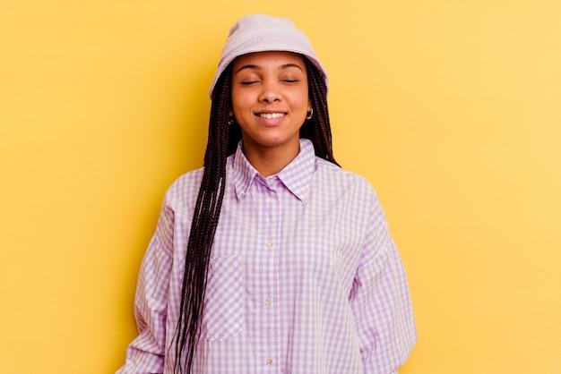 黄色の壁に隔離された若いアフリカ系アメリカ人女性は笑って目を閉じ、リラックスして幸せを感じます