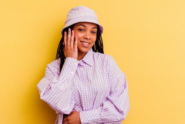 노란색 벽에 고립 된 젊은 아프리카 계 미국인 여자는 행복 하 게 웃음과 뱃속에 손을 유지하는 재미있다.