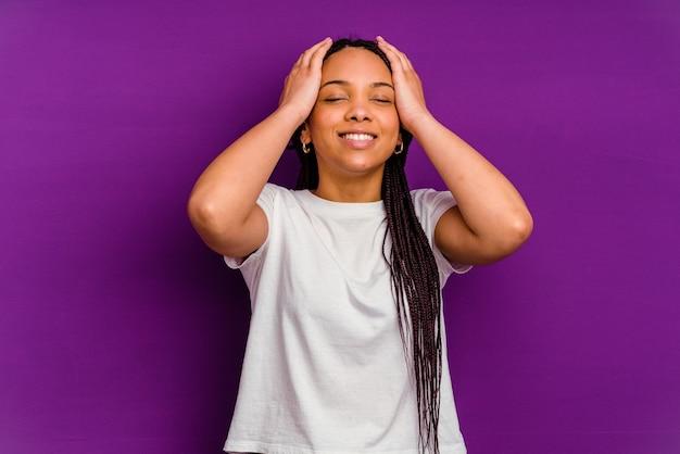 黄色の壁に隔離された若いアフリカ系アメリカ人の女性は、頭に手を置いて喜んで笑います。幸福の概念。
