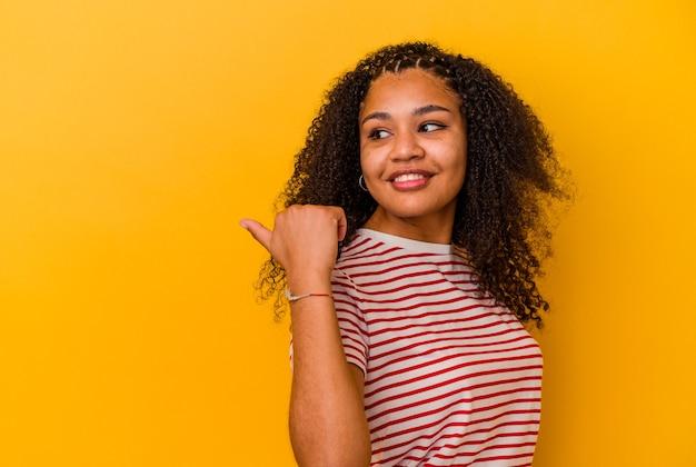 若いアフリカ系アメリカ人の女性は、親指の指を離れて、笑ってのんきな黄色の壁のポイントで隔離されました。