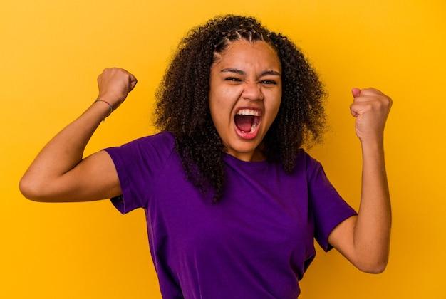 승리, 승자 개념 후 주먹을 높이 노란색 벽에 고립 된 젊은 아프리카 계 미국인 여자. 프리미엄 사진