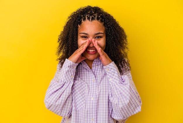 Молодая афро-американская женщина изолирована на желтой стене, говоря сплетню, указывая на сторону, сообщающую что-то.
