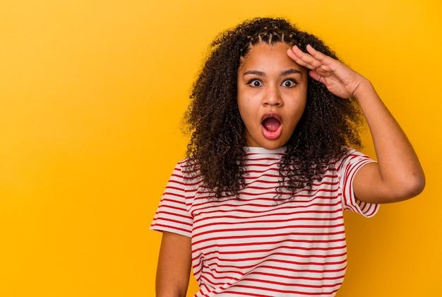 黄色い壁に孤立した若いアフリカ系アメリカ人女性は大声で叫び、目を開いたまま、手を緊張させます。