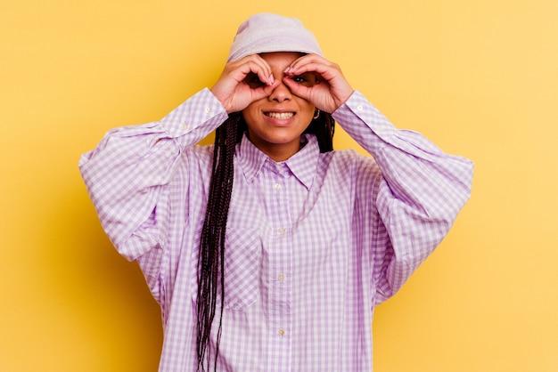 目の上の大丈夫な兆候を示す黄色の壁に分離された若いアフリカ系アメリカ人女性